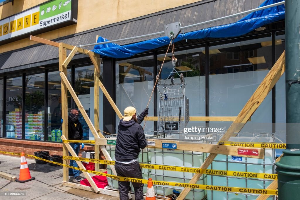 Small Supermarket employees disinfecting shopping carts, Covid-19 Virus response and social distancing, Philadelphia, Pennsylvania : News Photo