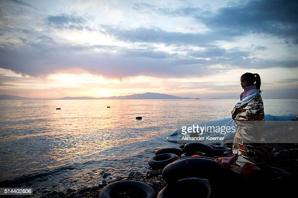 A small Syrian girl looks on during sunrise after arriving on an inflatable boat with other refugees crossing the sea from Turkey to Lesbos some 5...
