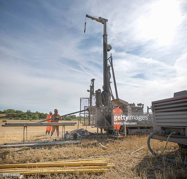 small team of workers operating drilling rig in field - モーペス ストックフォトと画像