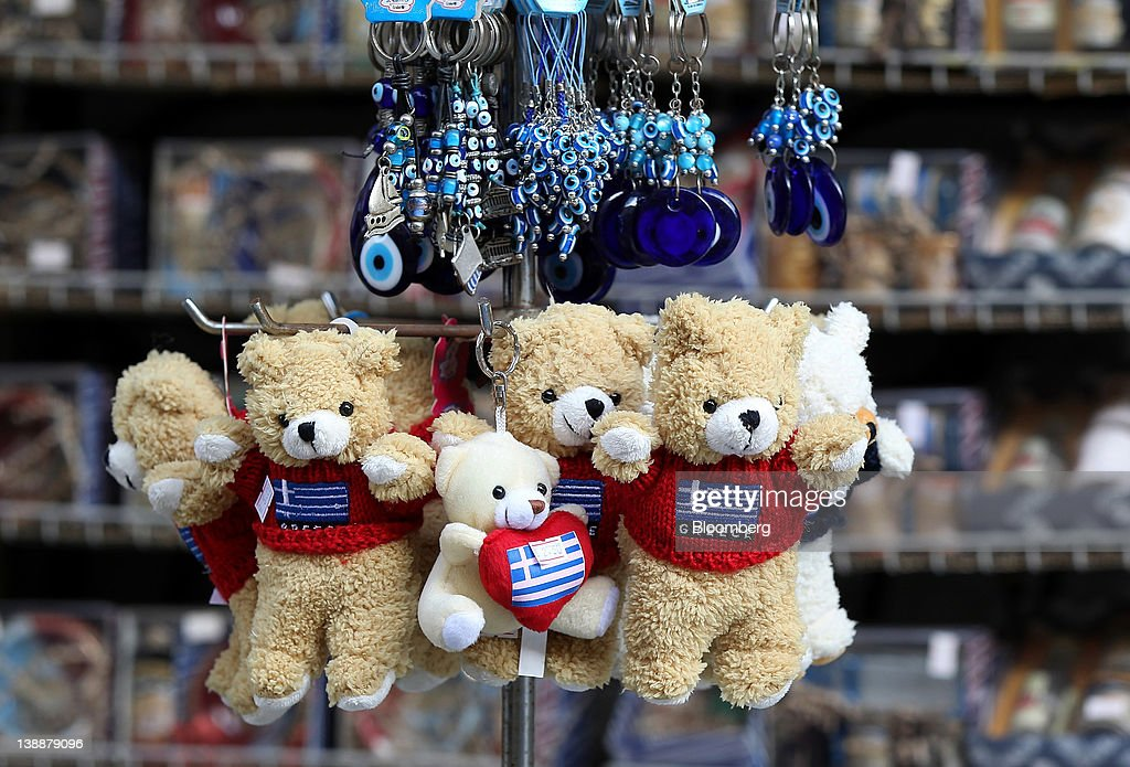 Small teddy bears wearing a red t-shirt covered with the Greek national flag are displayed for sale at a gift store in Athens, Greece, on Sunday, Feb. 12, 2012. Greek Prime Minister Lucas Papademos won parliamentary approval for austerity measures to secure an international bailout after rioters protesting the measures battled police and set fire to buildings in downtown Athens. Photographer: Simon Dawson/Bloomberg via Getty Images