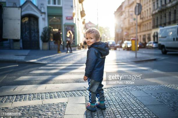 a small toddler boy standing by a road outdoors in city at sunset, looking back - cruzar fotografías e imágenes de stock