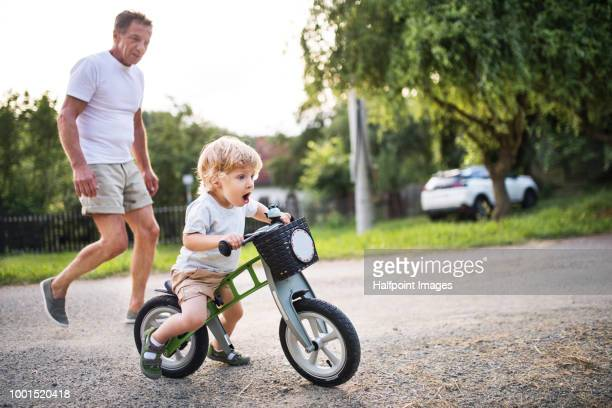 A small toddler boy with his grandfather riding a balance bike outdoors.