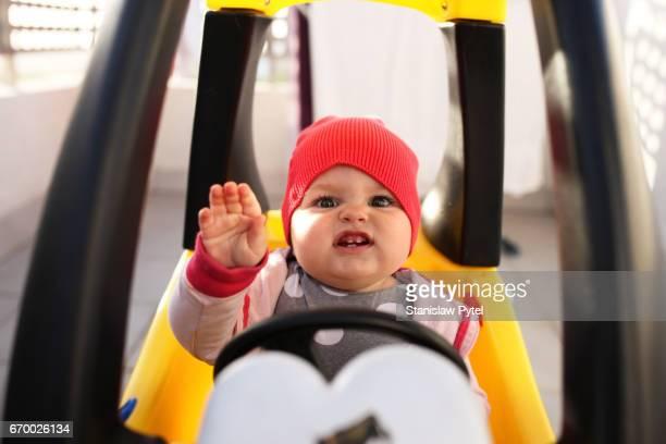 small toddler playing in toy car, smiling and waving hello - zwaaien gebaren stockfoto's en -beelden