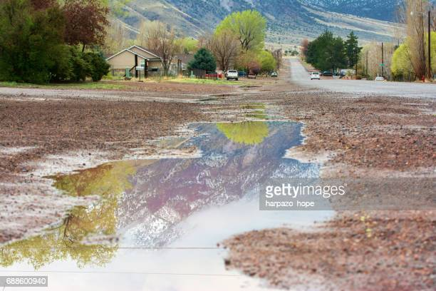 Small town road and a puddle with reflections of the mountains.
