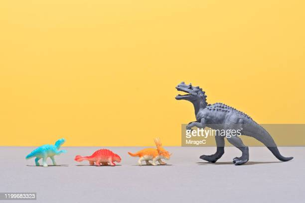 small toy dinosaurs facing a large toy dinosaur - dinosaur stock pictures, royalty-free photos & images