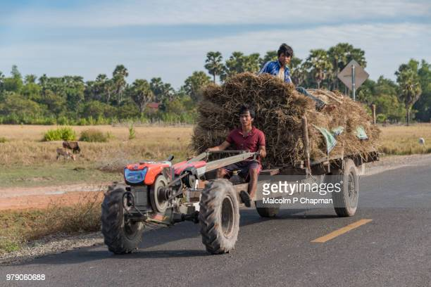 Small tractor and trailer loaded with hay on road near Kampong Them, Cambodia