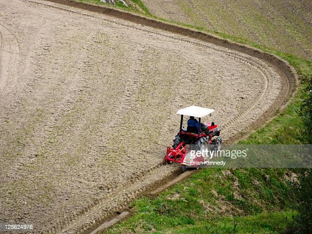 Small tractor tills soil