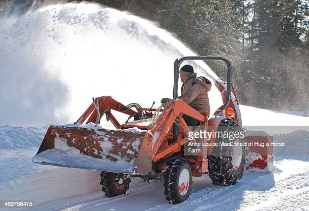 small tractor withsnow blower moving snow