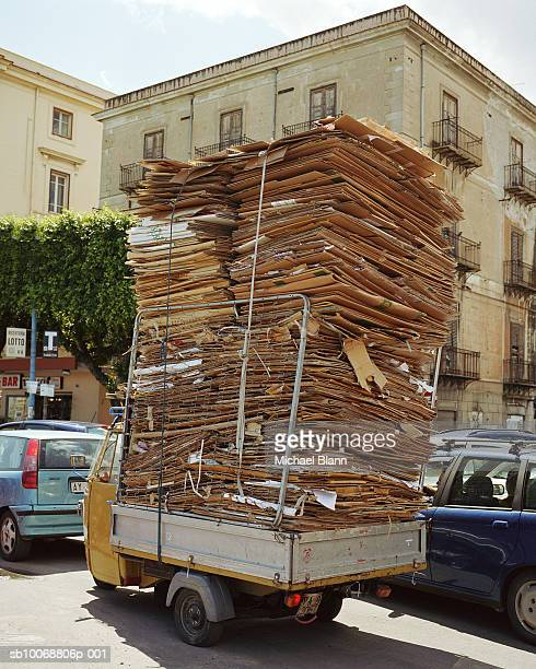 Small truck overloaded with cardboard in traffic jam