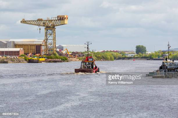 a small tug boat sailing in a city river - river clyde stock pictures, royalty-free photos & images