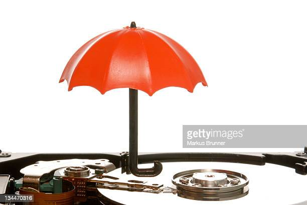 Small umbrella on a hard drive, symbolic image for data protection