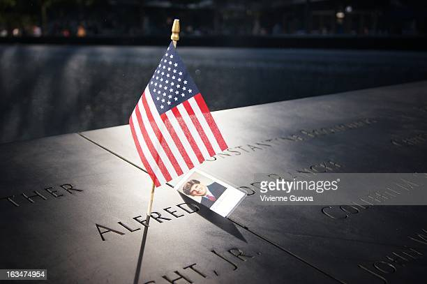 CONTENT] A small United States flag is placed within one of the engraved names of the victims of the World Trade Center attack on September 11 at the...