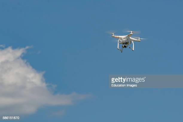 A small unmanned aerial vehicle with an attached camera that is hovering in the sky This type of aerial vehicle is known as a drone