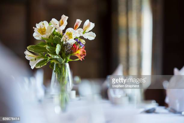 Small vase of fresh flowers on dividing table set out for dinner.