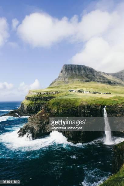 pequena aldeia acima um dos temas belas cachoeiras do mundo nas ilhas faroé - ilhas faeroe - fotografias e filmes do acervo