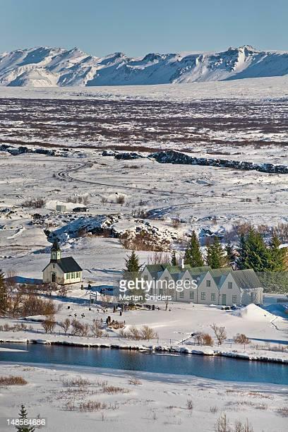 small village and surrounding mountains in winter. - merten snijders stock-fotos und bilder