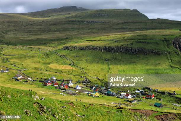 a small village between grassy mountains on an island - rainer grosskopf stock-fotos und bilder