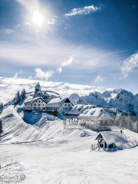 a small village on the mountain peak in wintertime - villaggio foto e immagini stock