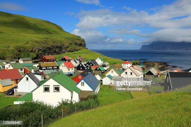 a small village situated on the sea coast with colorful houses between grassy hills - rainer grosskopf stock-fotos und bilder