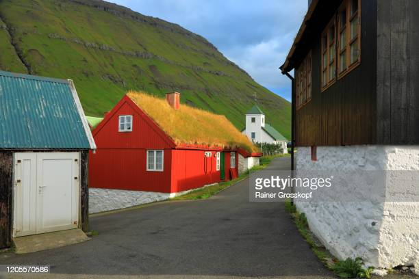a small village wit some red wooden houses with grassy roofs and a little white church - rainer grosskopf stock-fotos und bilder