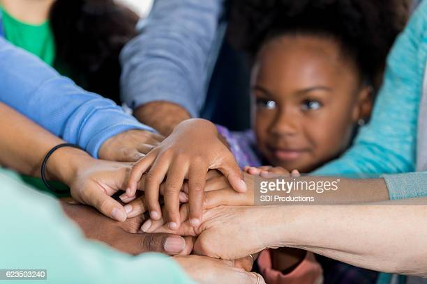 small volunteer puts hands together in unity with adult volunteers - carers stock photos and pictures