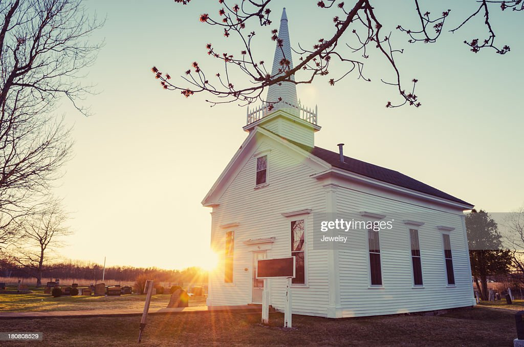 Small white church at sunrise in winter : Stock Photo