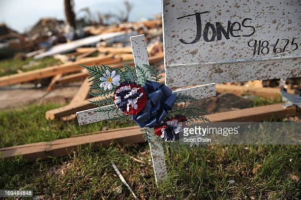 A small white cross sits in front of the home of Rick Jones a 54yearold postal worker who died when his house collapsed during Monday's tornado on...