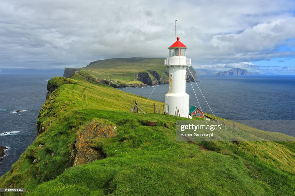 A small white lighthouse wit a red roof on top of grassy cliffs of Mykines Island : Stock-Foto