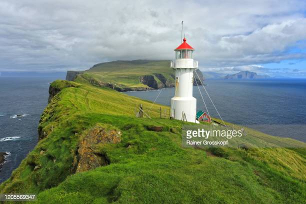 a small white lighthouse wit a red roof on top of grassy cliffs of mykines island - rainer grosskopf stock-fotos und bilder