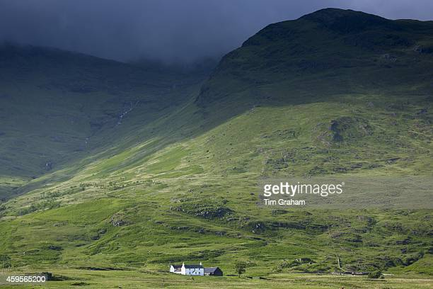 Small white solitary croft farmhouse nestling below mountain range by loch under moody sky on Isle of Mull in the Inner Hebrides and Western Isles of...