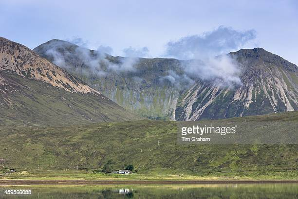 Small white solitary crofters cottage nestling below mountain range reflected in waters of the loch on Isle of Skye in the Highlands and Islands of...