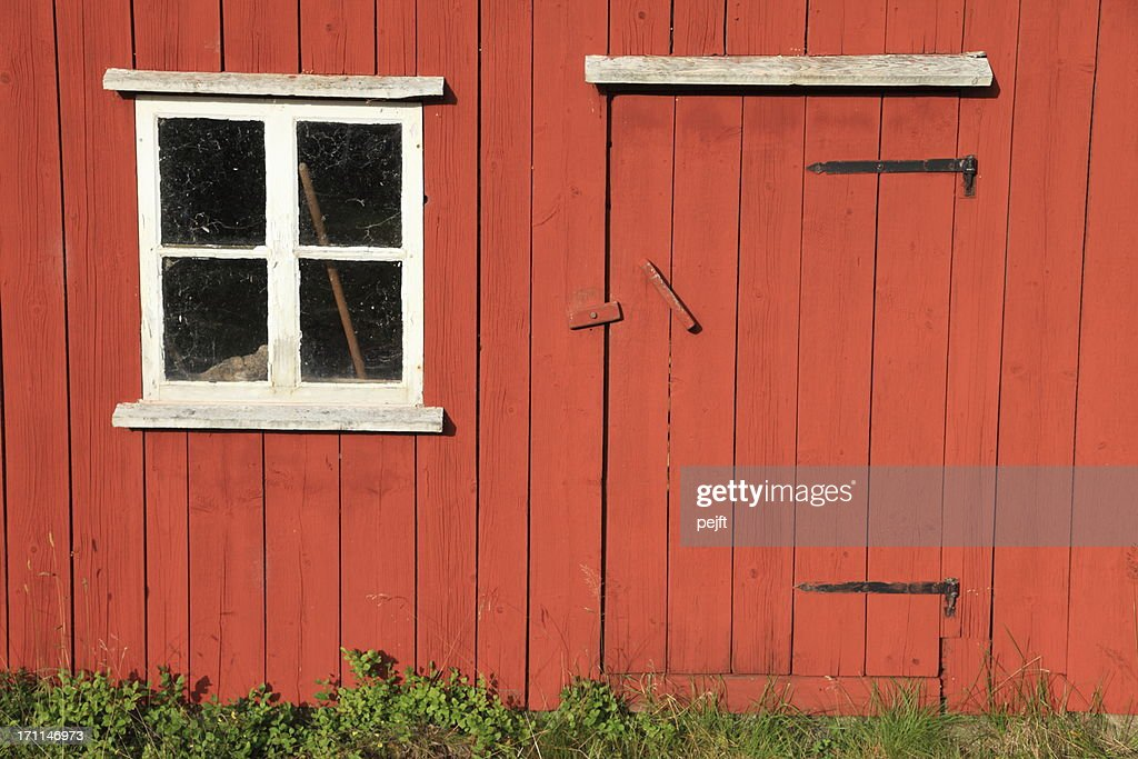 Small window and low door in a red wooden house : Stock Photo