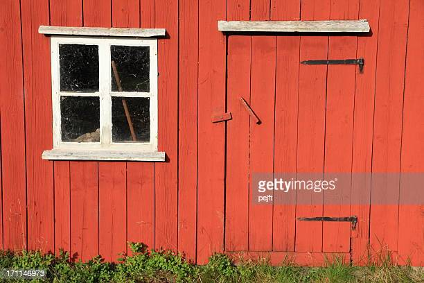 Small window and low door in a red wooden house