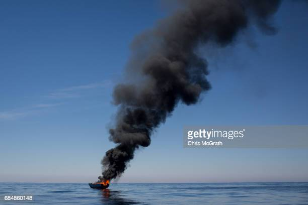 A small wooden boat used by refugees and migrants is seen burning after being set alight after all people were rescued by rescue crews from the...