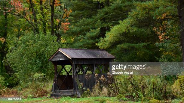 small wooden covered bridge in autumn, new england, usa - covered bridge stock pictures, royalty-free photos & images
