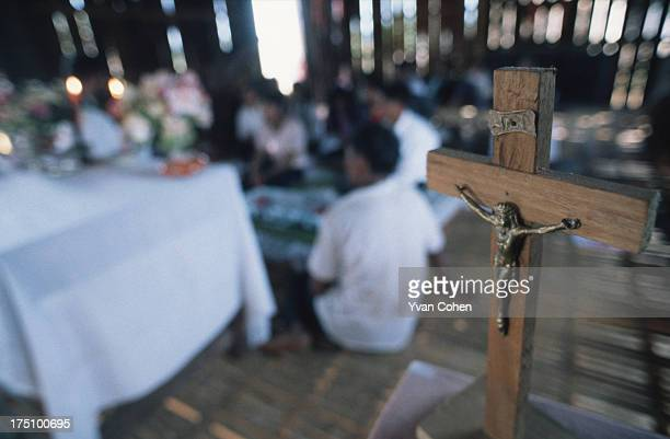 BOUSRA MONDOLKIRI CAMBODIA A small wooden crucifix stands in the foreground during a Catholic service in the Phnong village of Bousra in northeastern...