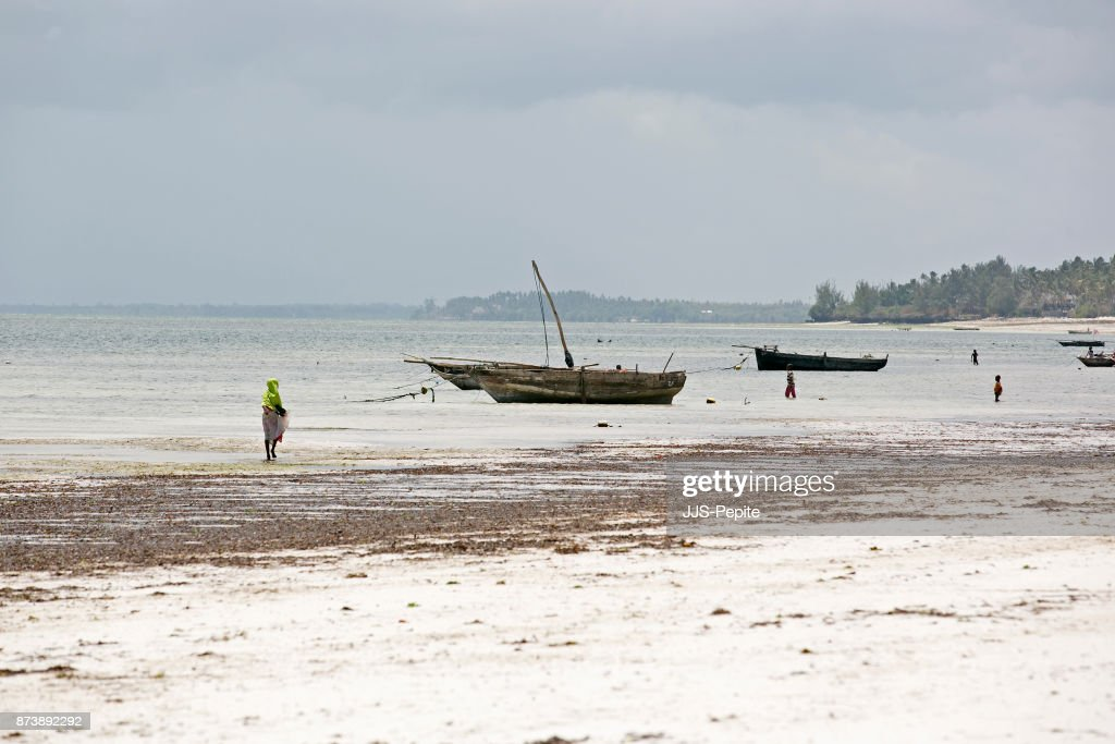 Small Wooden Fishing Dhow Moored In The Shallows Of A Tropical Island Stock Photo