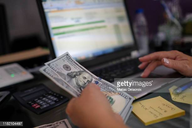 Small-business woman counts and pays her office stationery articles in USD dollars on June 26, 2019 in Caracas, Venezuela. Everyday, more Venezuelans...