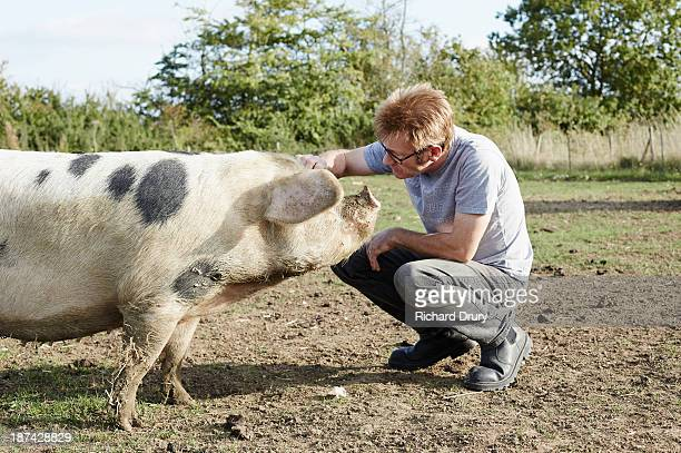 Smallholder on his farm with one of his pigs