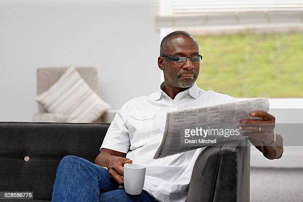smart african mature man reading newspaper - handsome 50 year old men stock photos and pictures