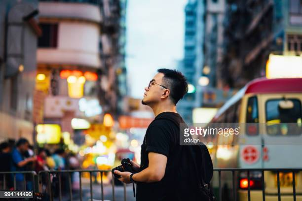 smart asian male tourist with camera exploring and sightseeing in local city street in hong kong - china oost azië stockfoto's en -beelden