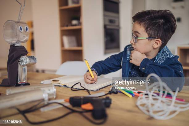 smart boy constructing a robot at home alone - child prodigy stock pictures, royalty-free photos & images