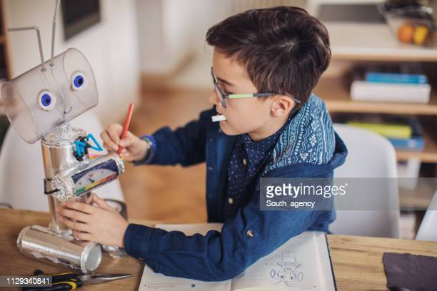 smart boy engineer constructing a robot - child prodigy stock pictures, royalty-free photos & images