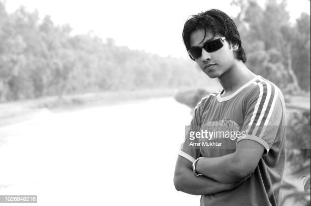a smart boy standing beside the water canal - lahore canal stock photos and pictures
