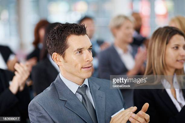 Smart business man applauding with colleagues during a seminar