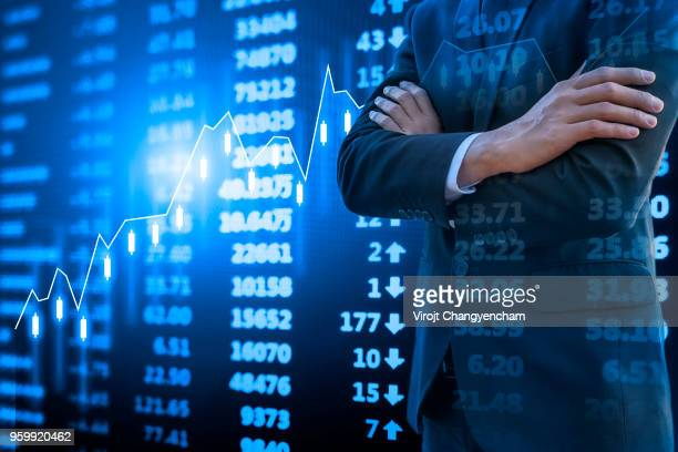 Smart businessman arms crossed and stock market chart, Financial data on electronic board background.