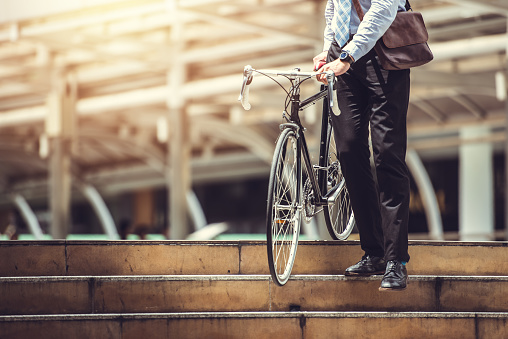 Smart Businessman Holding Bicycle goto Work on Urban Sidewalk in Rush Hour  - Eco Friendly and Lifestyles Concept 1051588194