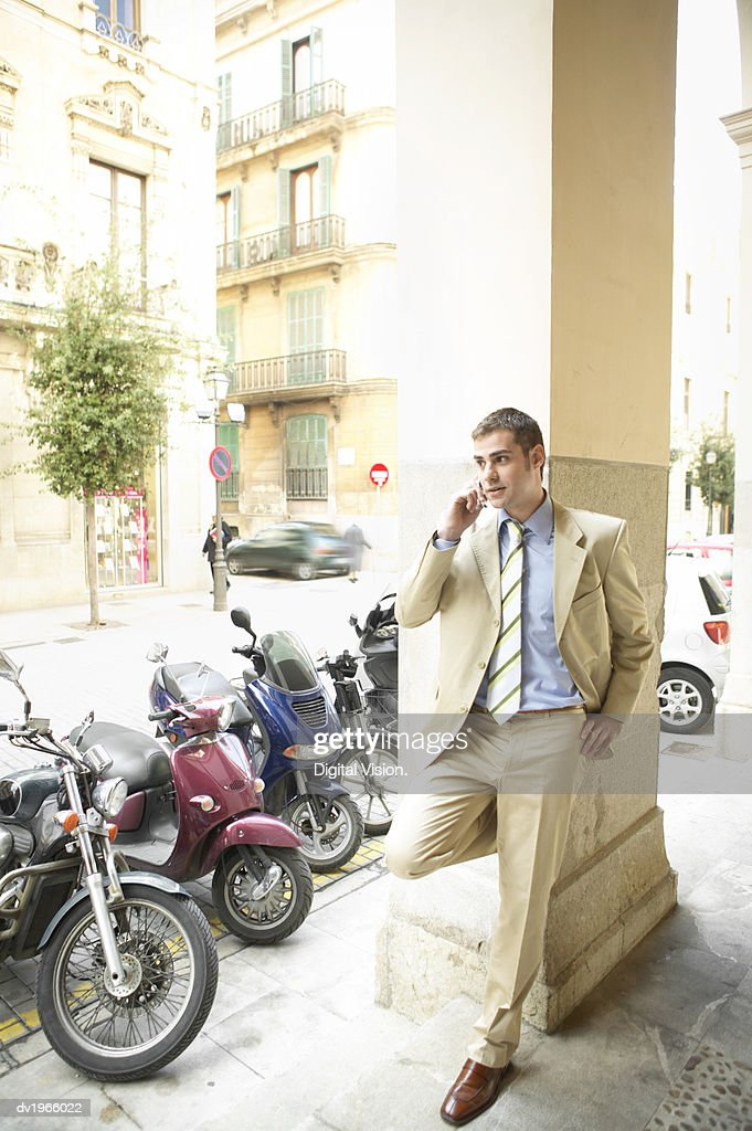 Smart Businessman Leans on a Column by the Street, Talking on His Mobile Phone : Stock Photo