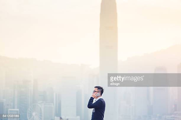Smart businessman talking on smartphone in city