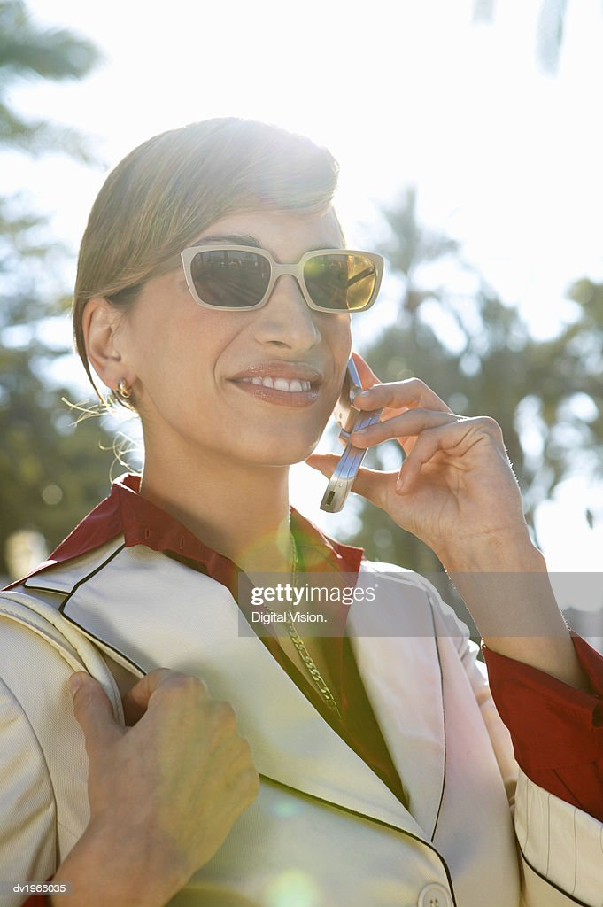 Smart Businesswoman in Sunglasses Talks on Her Mobile Phone : Stock Photo